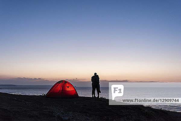 Romantic couple camping on the beach  kissing in twilight