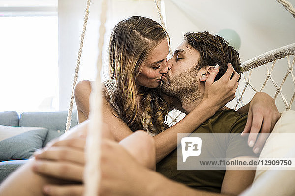 Affectionate couple kissing in hanging chair at home