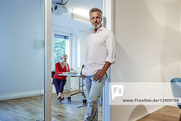 Portrait of mature man leaning against doorframe in office with colleague in background