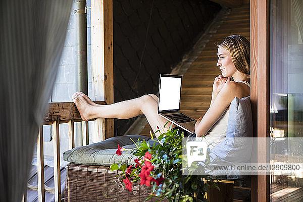 Woman relaxing on balcony using laptop