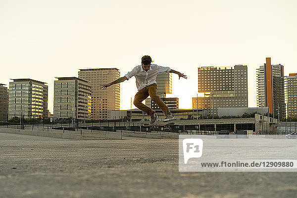 Young man doing a skateboard trick in the city at sunset