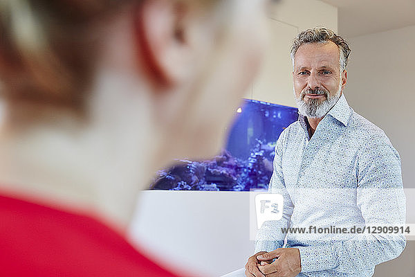 Mature man looking at female colleague in office