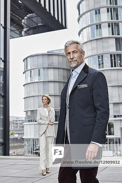 Germany  Duesseldorf  portrait of fashionable mature businessman in front of modern business building
