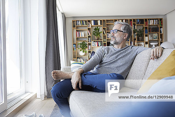 Mature man relaxing on couch in his living room looking out of window