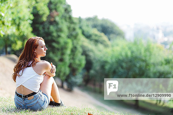 Redheaded woman relaxing on hill in a park