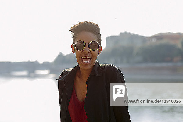 Italy  Verona  portrait of laughing young woman wearing sunglasses