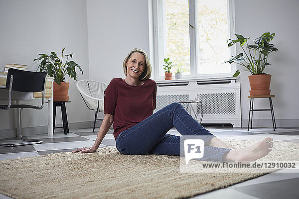 Smiling mature woman sitting on the floor at home