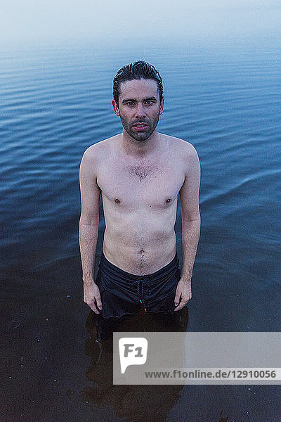Man with bare chest standing in lake