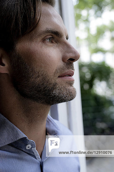 Close-up of man looking out of window