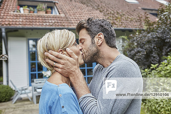 Couple kissing in front of their home