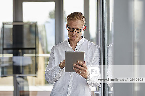 Businessman using tablet at the window in office