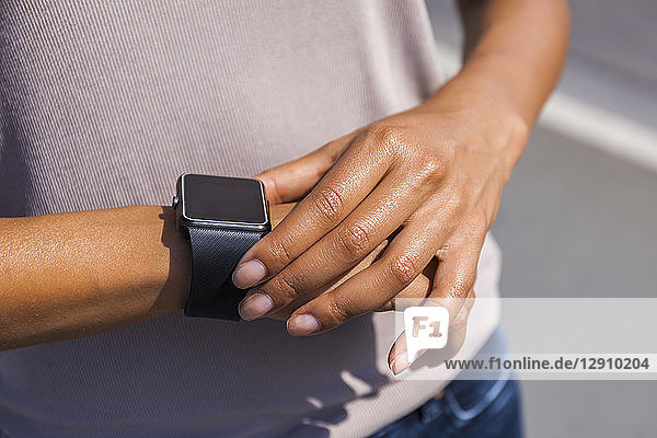 Woman's hand adjusting settings of smartwatch  close-up