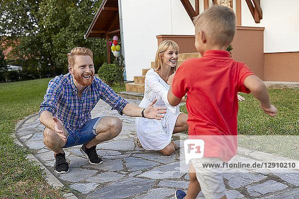 Boy running towards happy parents on garden path
