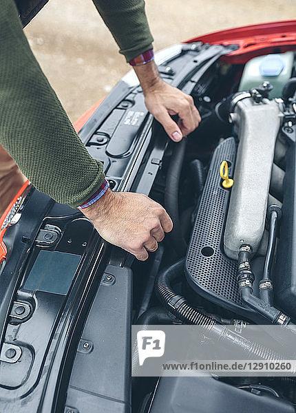 Close-up of man checking car engine
