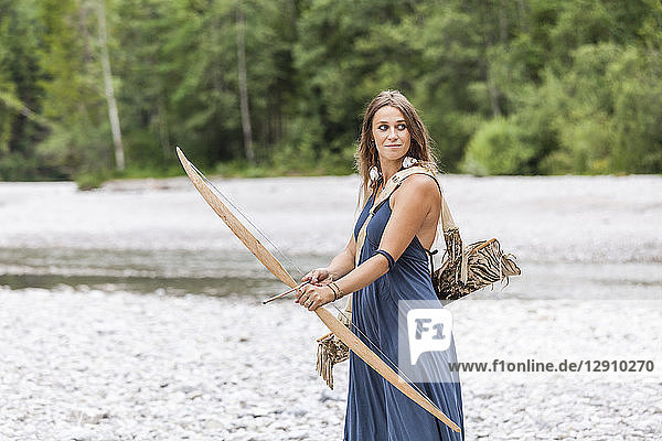 Archeress with bow and arrow in the nature