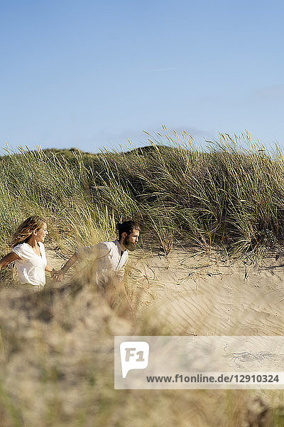 Young couple having fun in the dunes,  running hand in hand
