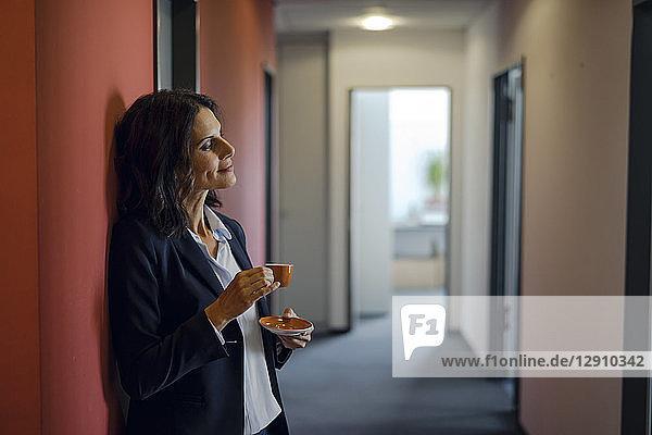Mature businesswoman standing in office corridor  drinking coffee