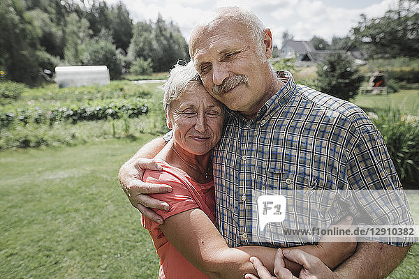 Portrait of happy senior couple embracing each other in the garden