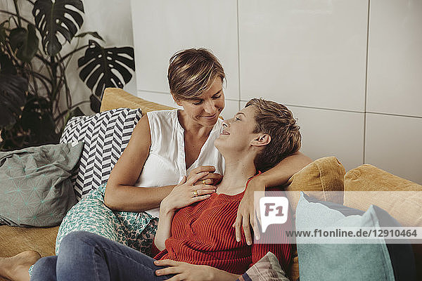 Happy lesbian couple cuddling on couch