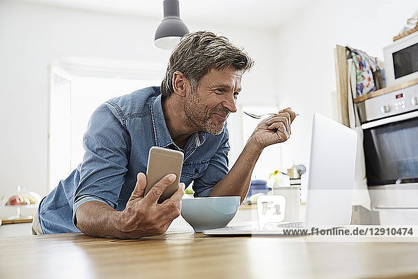 Mature man in his kitchen having breakfast  while checking his laptop