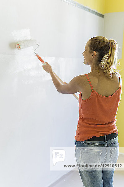 Young woman painting wall at new home