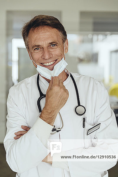 Portrait of a doctor  removing surgical mask  smiling