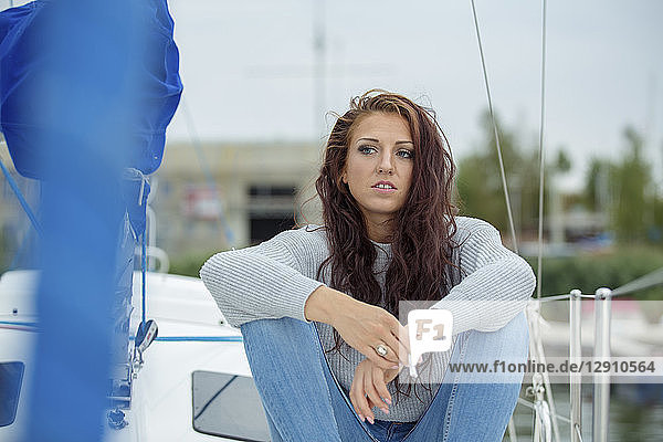 Woman sitting on sailing boat  waiting  smoking cigarette