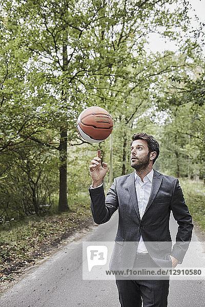 Businessman balancing basketball on rural road