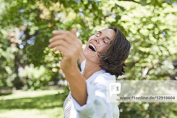 Happy mature woman dancing in nature