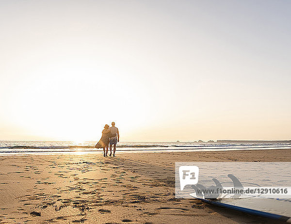 Romantic couple doing a beach stroll at sunset