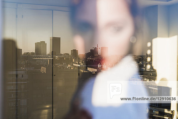 Spain  Madrid  blurred view of woman behind windowpane with reflection of the city