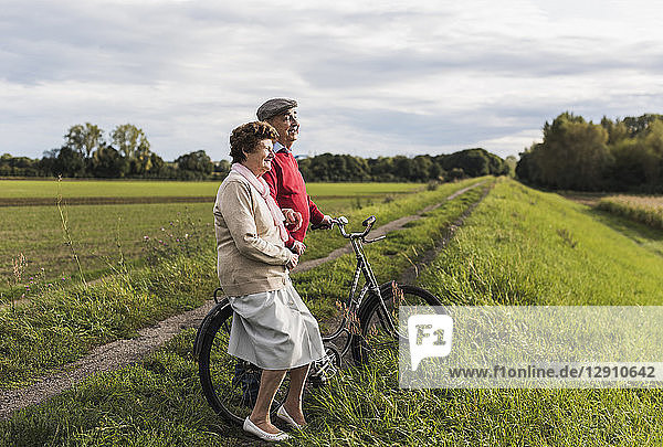 Senior couple with bicycles in rural landscape