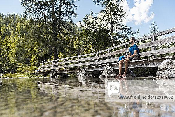 Austria  Tyrol  Hiker at Lake Seebensee sitting on boardwalk  taking a break