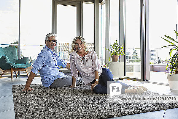 Portrait of smiling mature couple relaxing at home sitting on carpet