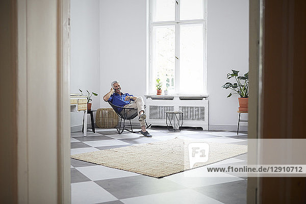 Smiling mature man on cell phone at home