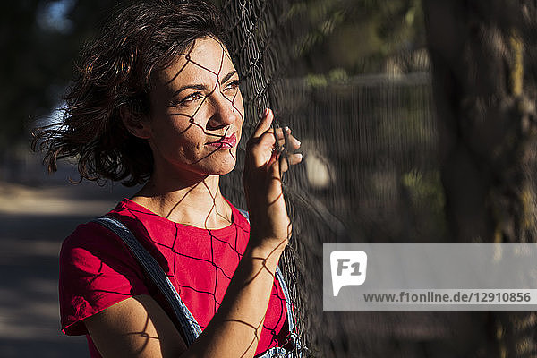 Portrait of smiling woman with shadow of wire mesh fence on her face looking at distance