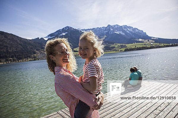 Austria  Tyrol  Walchsee  happy mother carrying daughter at the lake