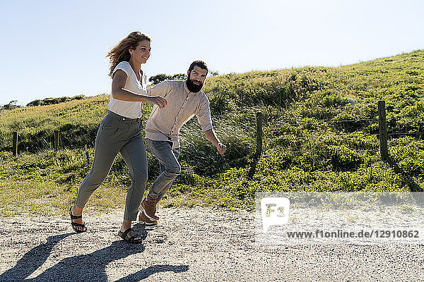 Young couple having fun in the dunes  running hand in hand
