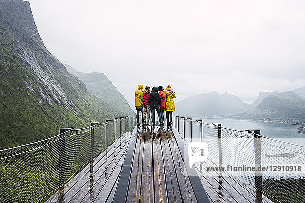 Norway  Senja island  rear view of friends standing on an observation deck at the coast