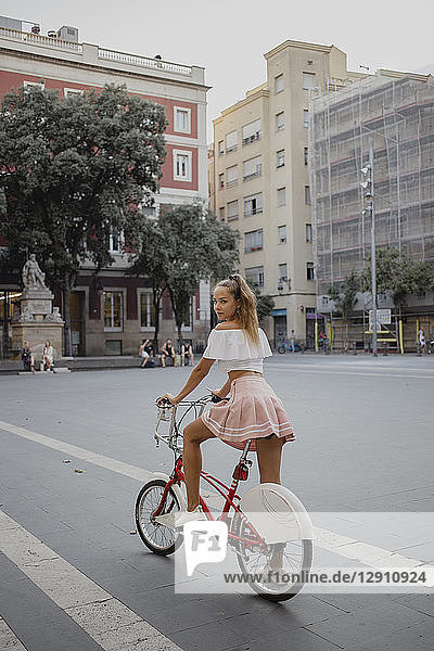 Fashionable young woman exploring Barcelona with a bicycle