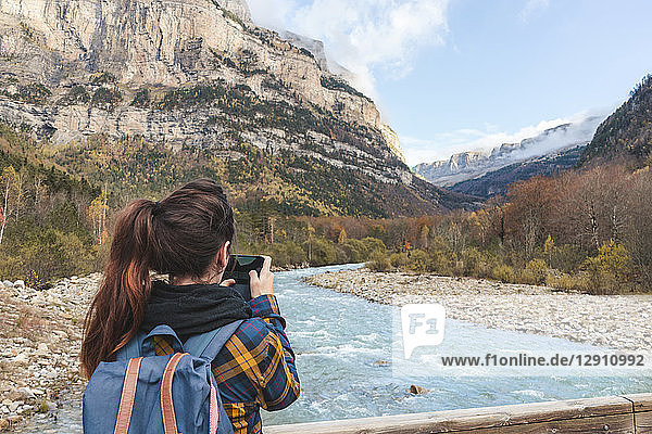 Spain  Ordesa y Monte Perdido National Park  back view of woman with backpack taking photo