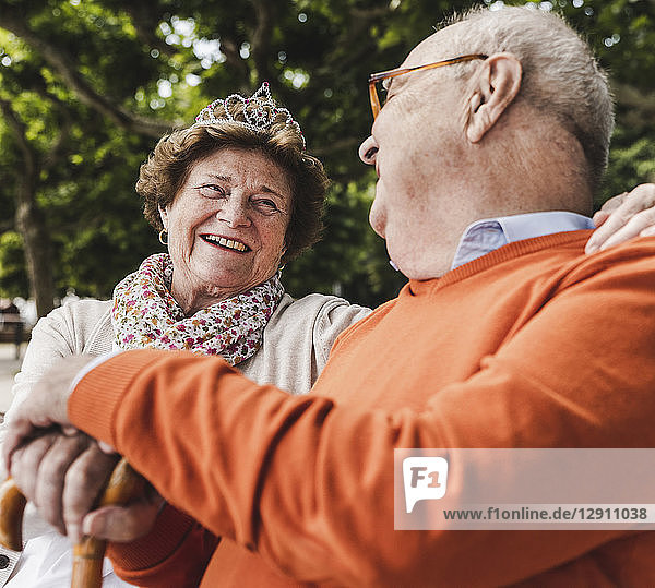 Happy senior couple sitting in park  woman wearing crown