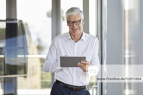 Businessman leaning on window  using digital tablet