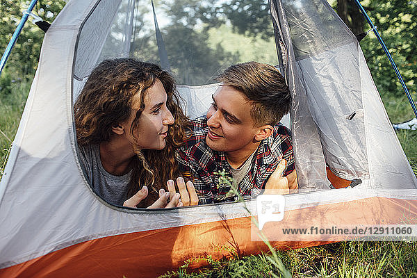 Happy young couple lying in tent  talking
