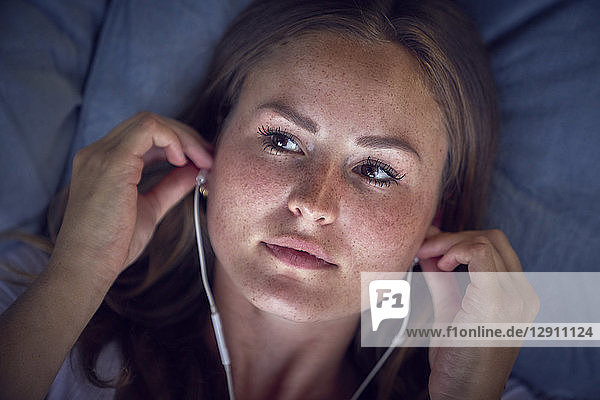 Young woman lying on cushion  listening music with earphones