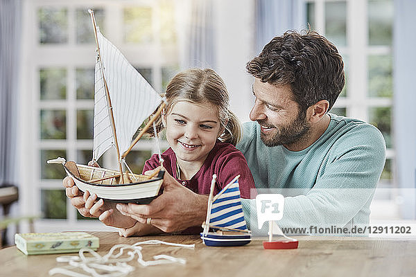 Happy father and daughter playing with model boat at home