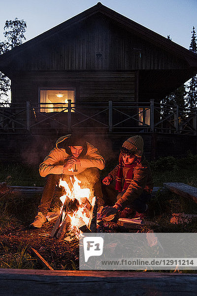 Friends sitting at a campfire,  watching the flames