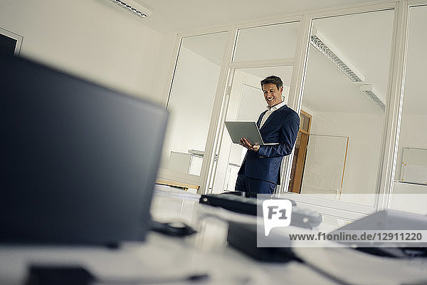 Businessman standing in office  using laptop