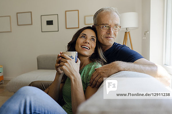 Happy mature couple sitting on couch at home