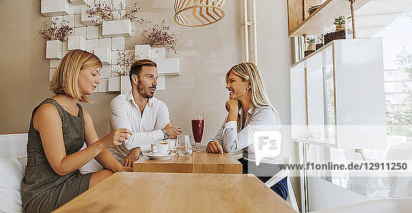 Three friends meeting in a cafe